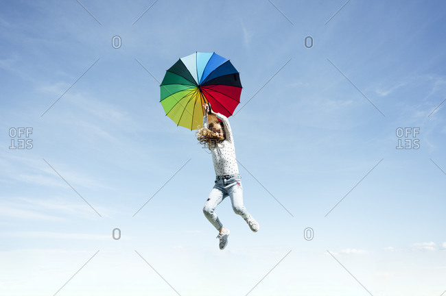 Low angle view of girl jumping with multi colored umbrella against blue sky