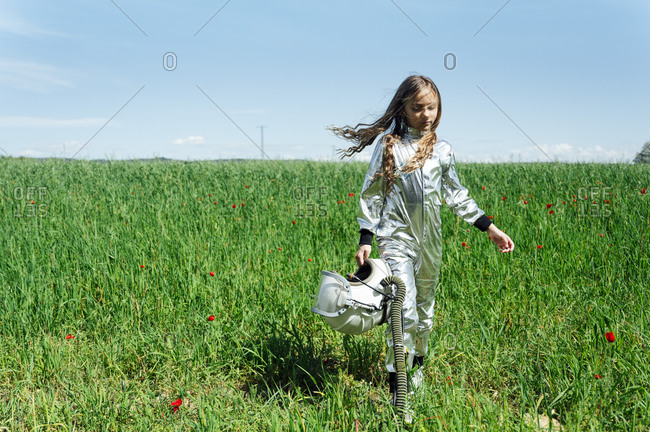 Full length of girl in astronaut costume walking with helmet on grass against sky