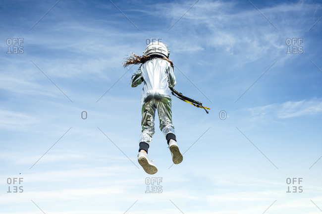 Low angle rear view of astronaut girl in space suit jumping on sunny day