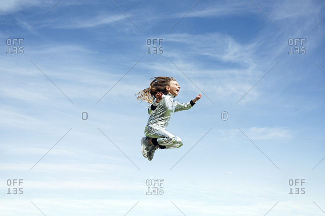 Full length of carefree girl in space suit jumping against blue sky