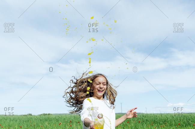 Cheerful girl splashing juice from bottle while enjoying against sky on sunny day