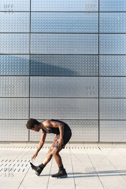 Young man stretching at a metallic shining wall