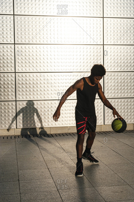 Young man playing basketball at a metallic shining wall