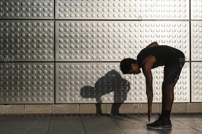 Young man exercising at a metallic shining wall