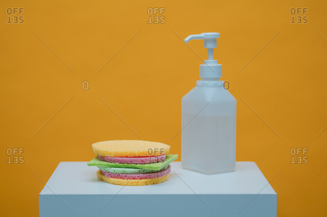 Cleaning sponges and sponge cloth in shape of a burger by spray bottle with sanitizer