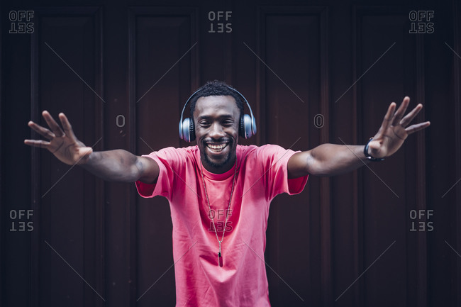 Portrait of laughing man wearing pink t-shirt listening to music with headphones