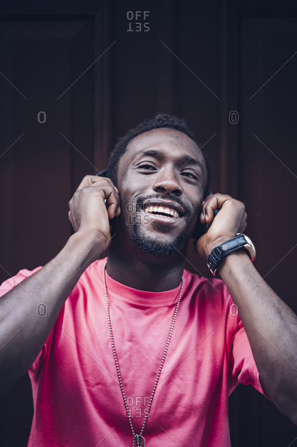 Portrait of happy man wearing pink t-shirt listening to music with headphones
