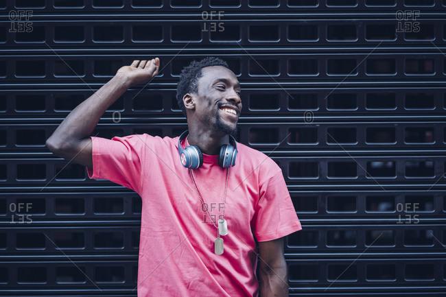 Smiling man with headphones wearing pink t-shirt