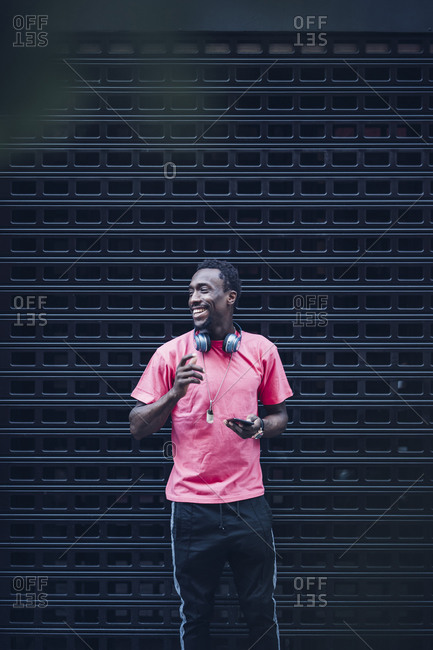 Portrait of smiling man with headphones and smartphone wearing pink t-shirt