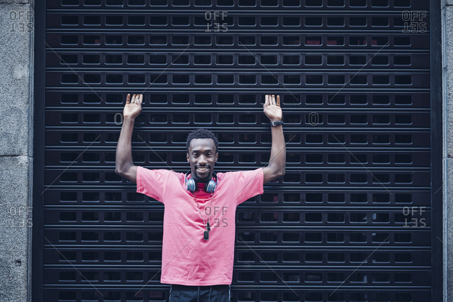 Portrait of smiling man with headphones wearing pink t-shirt