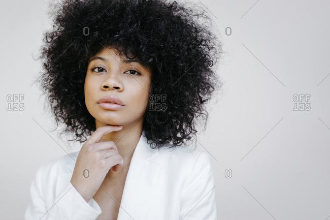 Black woman- wearing white suit- standing in front of white wall- looking pensive