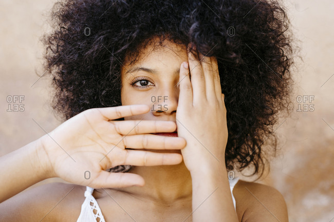 Black woman standing in front of wall- covering one eye and mouth with hands
