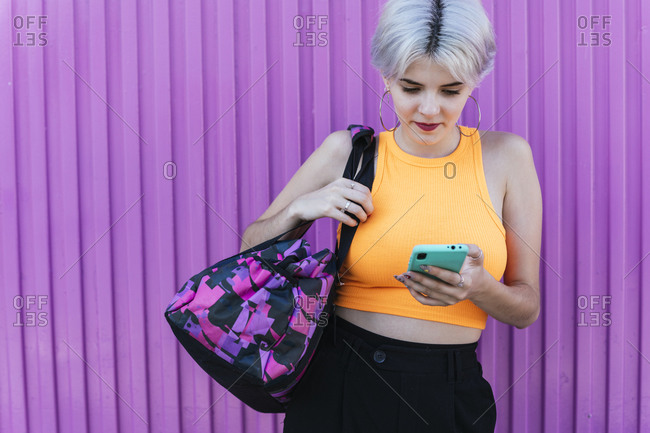 Blond woman with bag- using smartphone in front of purple wall