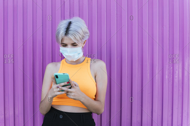 Blond woman with face mask- using smartphone in front of purple wall