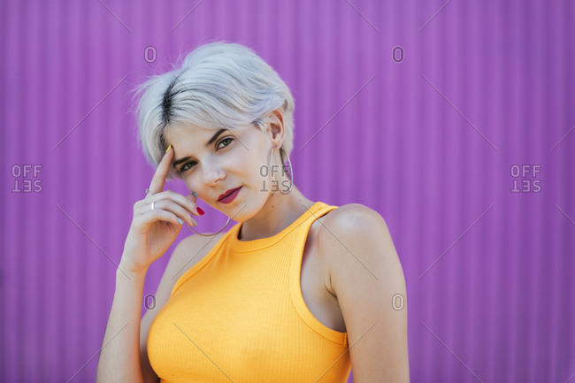 Beautiful blond woman standing in front of purple wall- portrait