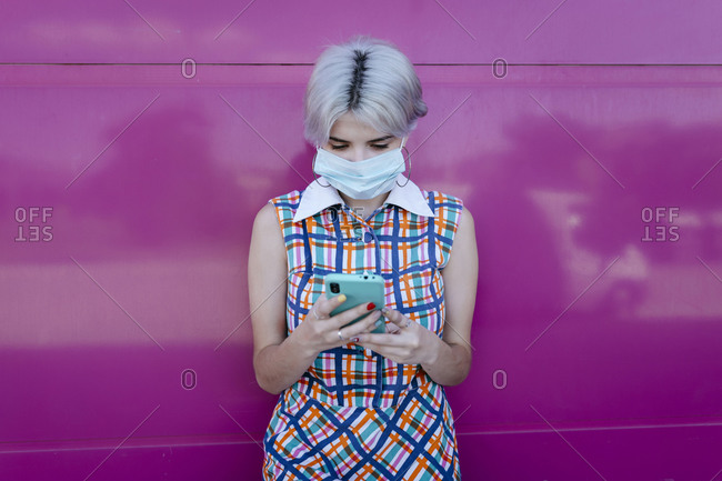 Young woman wearing mask using smart phone while standing against pink glass wall