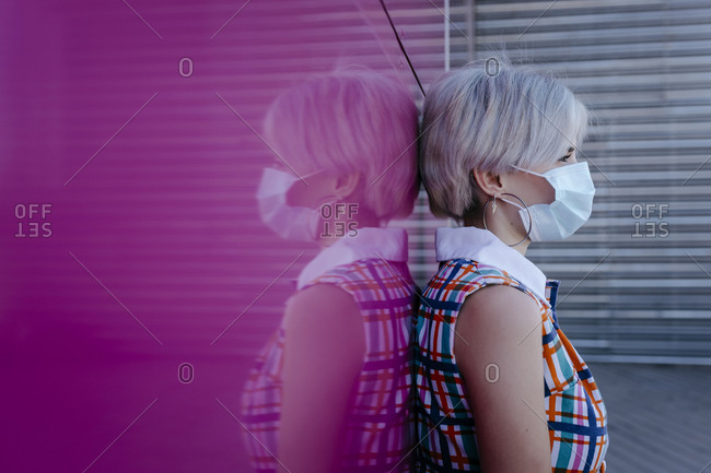 Young woman wearing mask standing against pink glass wall