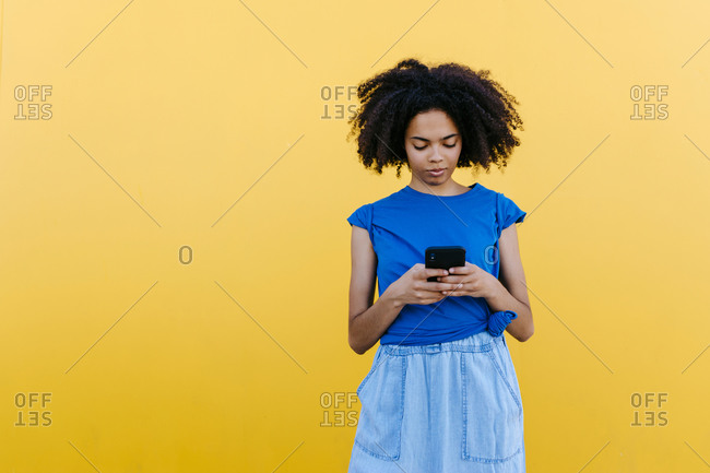 Young woman using smartphone in front of yellow wall