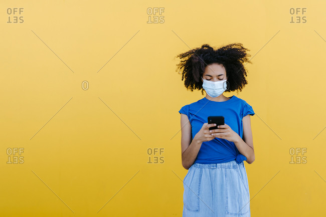 Young woman wearing protective mask- using smartphone in front of yellow wall