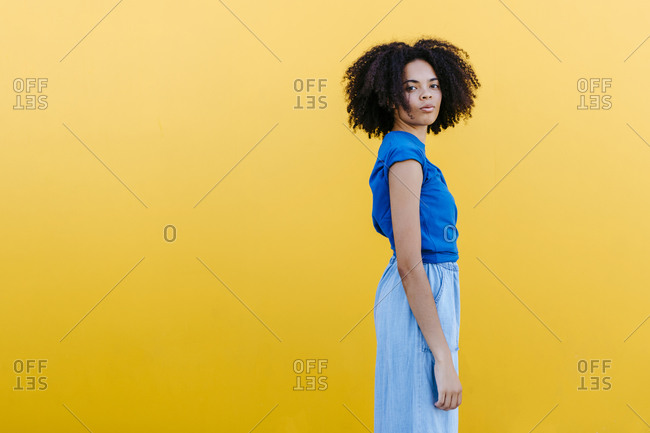 Pretty woman standing in front of yellow wall