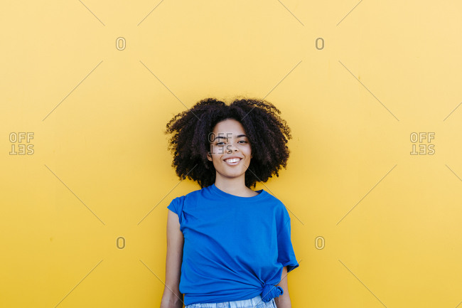 Pretty woman standing in front of yellow wall- smiling happily
