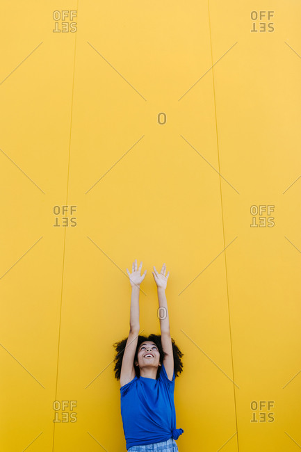 Smiling woman reaching up at yellow wall