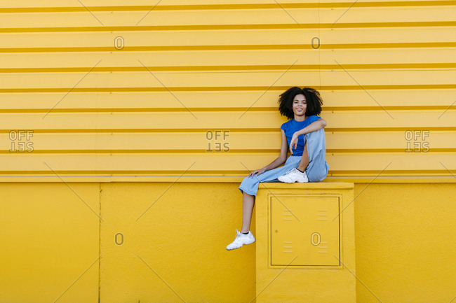 Pretty woman sitting on platform in front of yellow wall- smiling