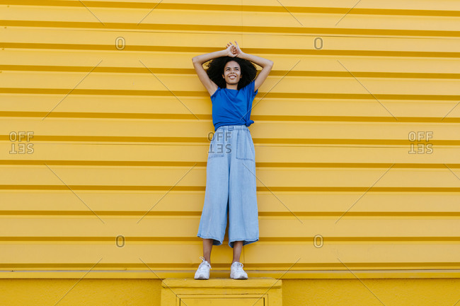 Smiling woman standing on platform in front of yellow wall