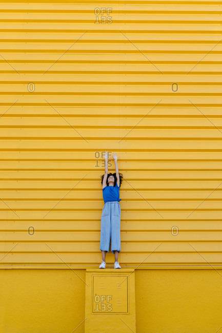 Smiling woman reaching up at yellow wall- standing on platform