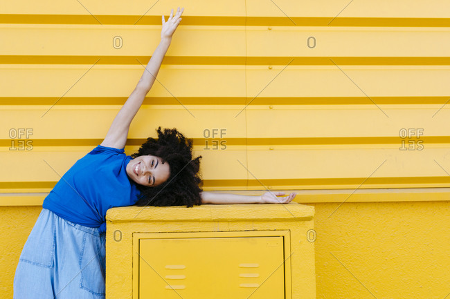 Dreamy woman bending sideways over platform in front of yellow wall