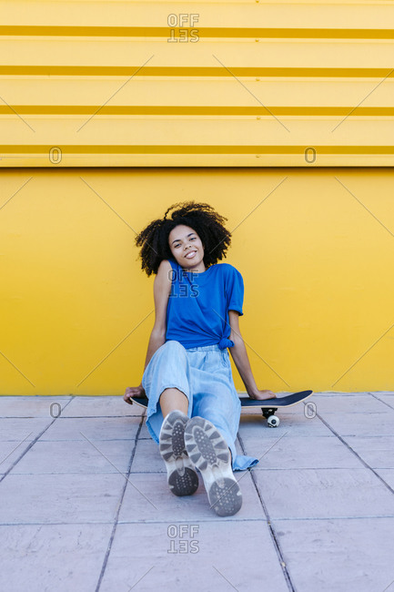 Smiling young woman sitting on skateboard in front of yellow wall