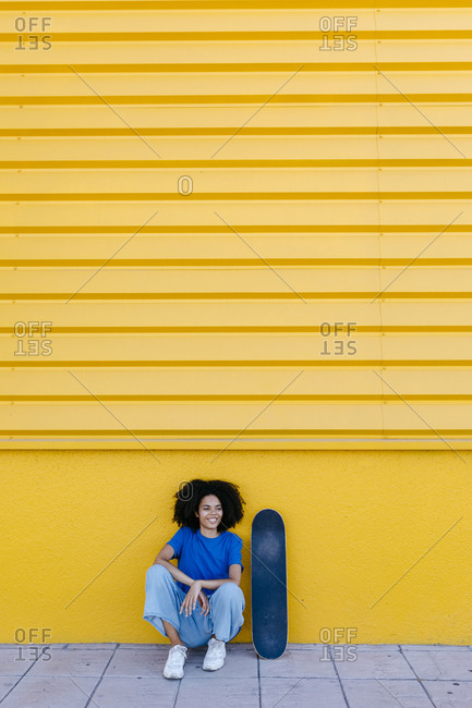 Young woman with skateboard sitting in front of yellow wall