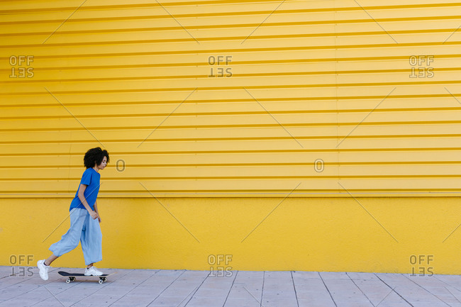 Young woman skateboarding in front of yellow wall