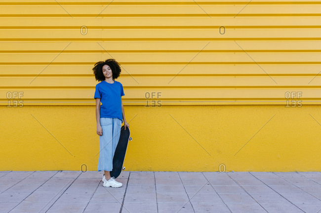 Young woman with skateboard standing in front of yellow wall