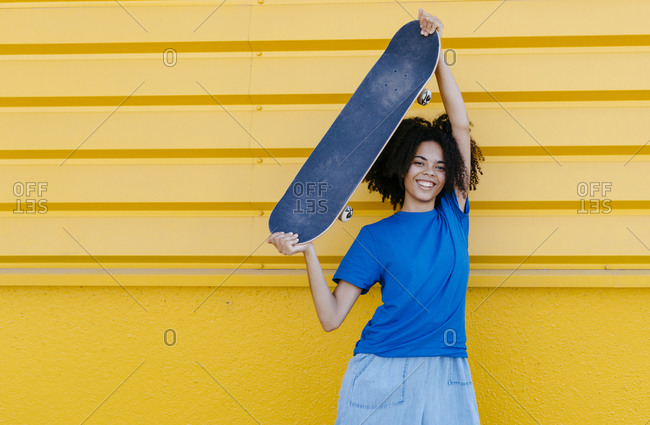 Smiling young woman holding skateboard aloft