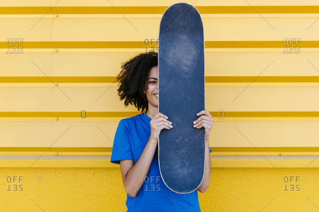 Young woman holding skateboard in front of face- looking at camera