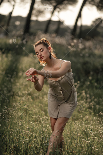 Full shot of a young female ballet dancer dancing in the middle of a forest full of trees and flowers.