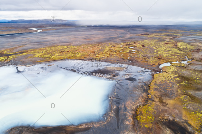 Aerial view of colorful desolate landscape with lake and rain showers, Sprengisandur, highlands of Iceland