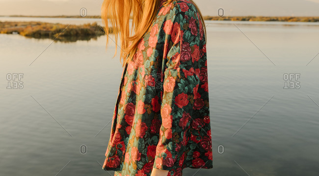 Woman wearing a designer floral outfit while walking by the sea