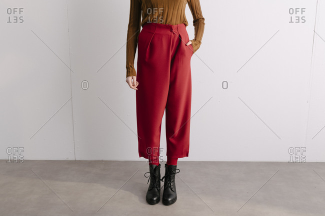 Model wearing red designer slacks and brown sweater with combat boots