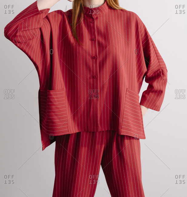 Studio shot of a model wearing a red striped designer suit
