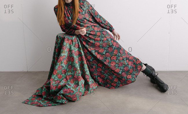Female model leaning on table covered in fabric to match her designer floral dress