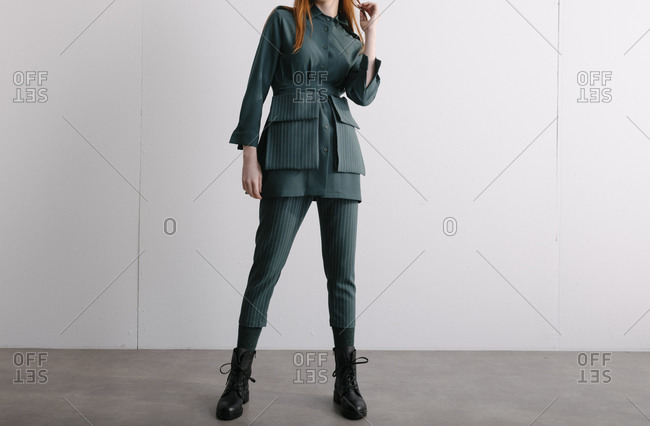 Young model wearing a green designer outfit and combat boots