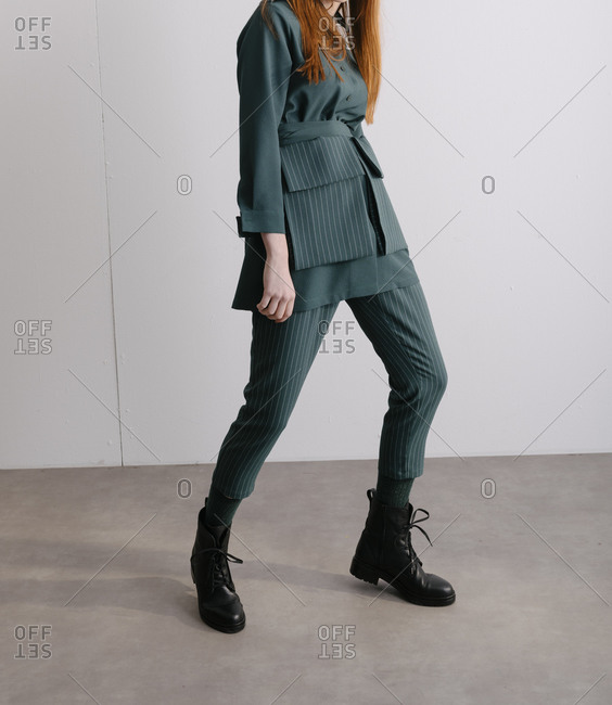 Model wearing a green designer suit and combat boots
