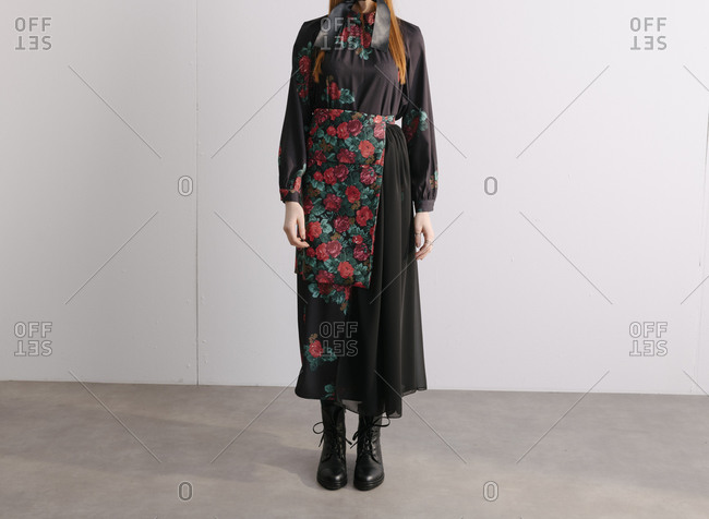 Young model in a black designer dress with floral pattern