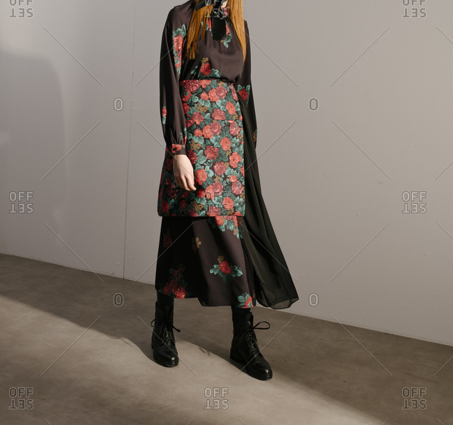 Stylish young woman in a black designer dress with floral pattern