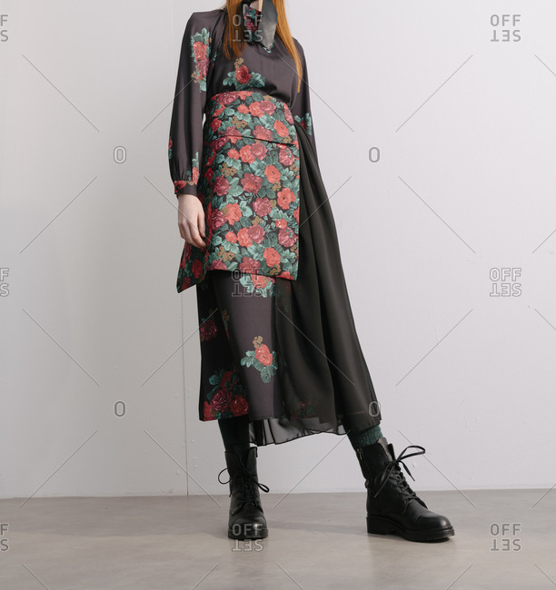 Low angle view of a stylish young woman in a black designer dress with floral pattern