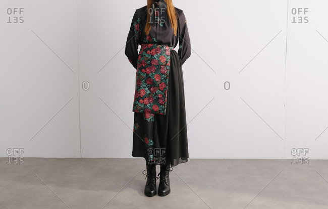 Young model wearing a black designer dress with floral pattern