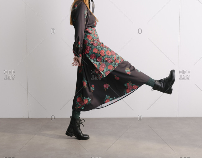 Model wearing a black designer dress with floral pattern and taking a large step