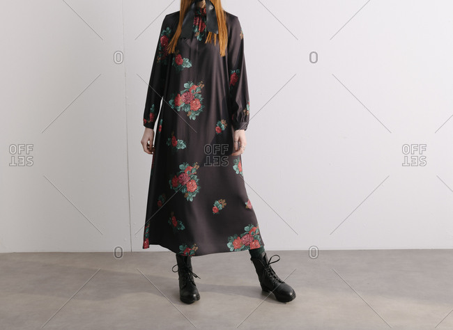 Young model wearing a black dress with red floral pattern